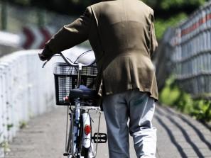 Vieux marchant à côté de son vélo
